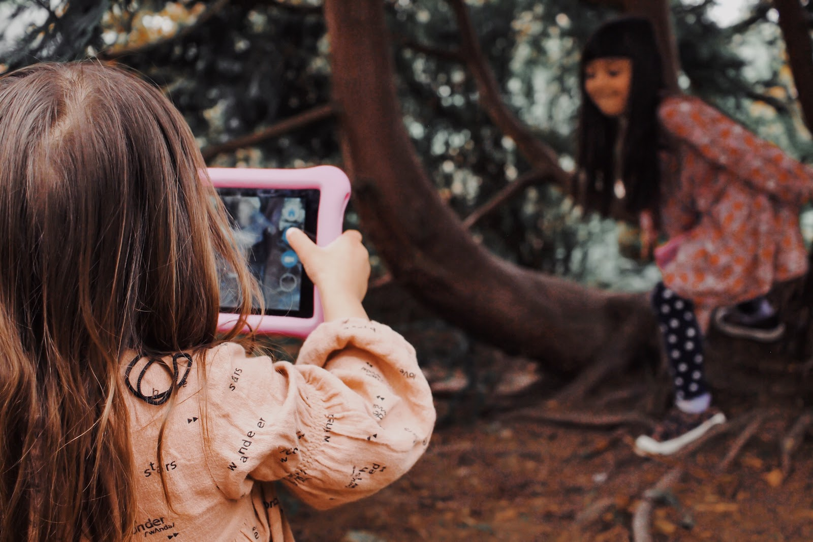 girl photographs sister with iPad