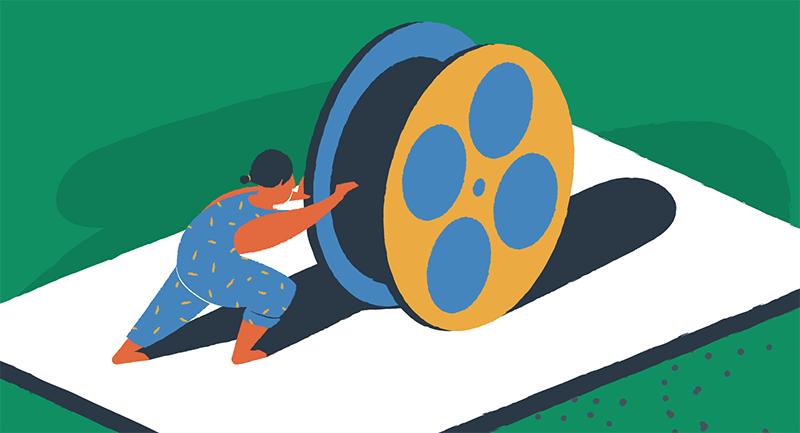 man rolling giant reel of film
