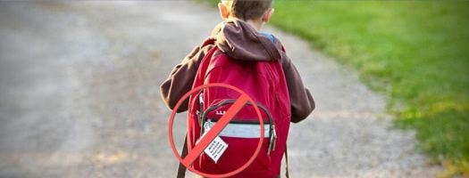 Child Wearing Backpack with Bus Name Badge Walking Away