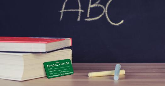 "Books, Visitor Name Tag, and Chalk on a Desk in Front of a Blackboard with ""ABC"" Written in Chalk"