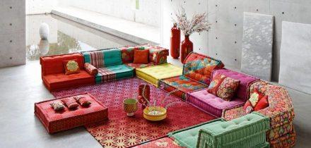 Ryškiaspalvė sofa iš atraižų gabaliukų žaismingai pagyvina niūrų interjerą
