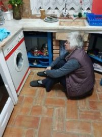Nancy sat on the floor in front of the washing machine
