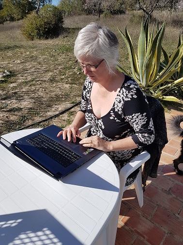Nancy typing on a laptop outside