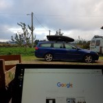 View over a laptop screen to a car with roof box
