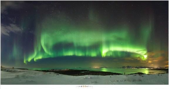 Fisheye opname vanaf het strand van Laukvik/Straumnes. Een prachtig fel poollicht dat reflecteert in het water van de Noorse Zee