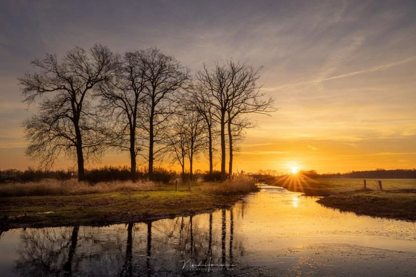 De zonsopkomst, niet rood met met subtiele gele kleuren die reflecteren in de Kaweise Loop.