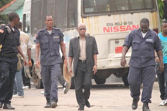 Liberan police officers escort Lieutenant Hotie