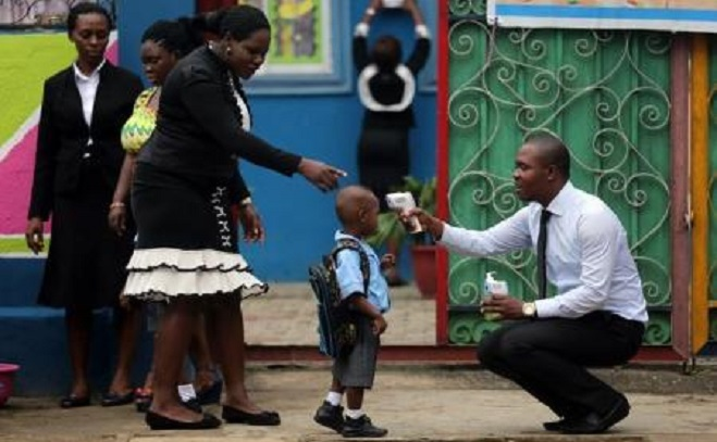 """A school official takes a pupil""""s temperature using an infrared digital laser thermometer in front of the school premises, at the resumption of private schools, in Lagos in this September 22, 2014 file photo.  REUTERS/Akintunde Akinleye"""