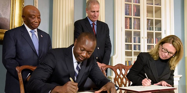 Minister Konneh and MCC chief executive officer Dana J. Hyde sign the deal while Vice President Boakai and a US official look on