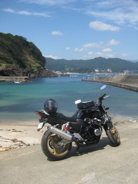 The CB400 in front of the ocean, on a small concrete harbour wall in front of the beach.