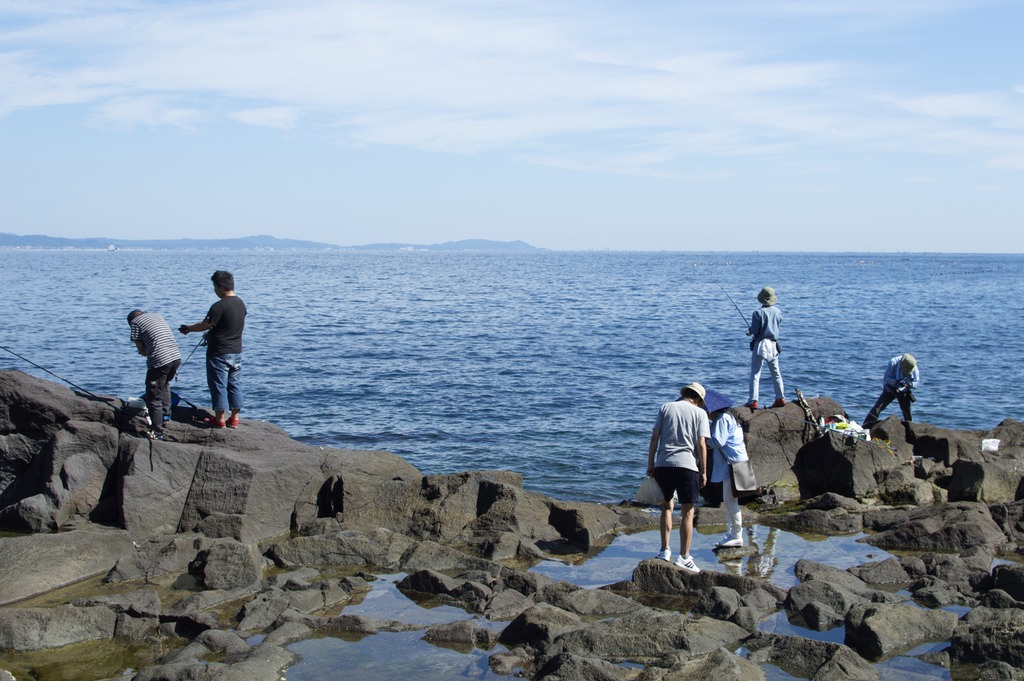 People fishing off some rocks by the ocean