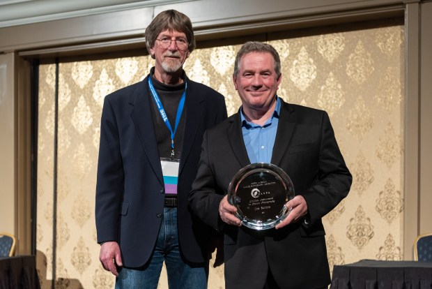 Joel Sartore receives NANPA's Lifetime Achievement Award from NANPA President Gordon Illg at the 2019 Nature Photography Summit. Photo by Frank Gallagher.