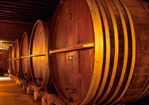 Fine wine ages in huge 100 year old oaken casks in a cool wine cellar.