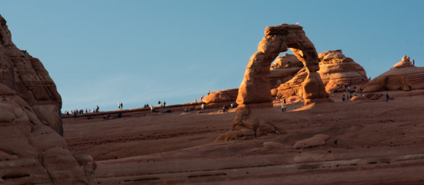 Crowds of tourists and photographers start to gather by Delicate Arch hours before sunset.