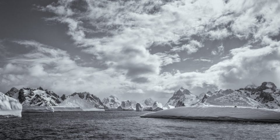 Icebergs, mountains and skies under calm seas and good weather.