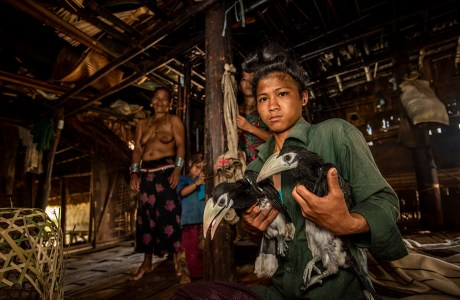 "2020 Showcase, Best in Show: Conservation. ""Desperate Deals, Mro Village, Chittagong Hill Tracts, Bangladesh"" © Scott Trageser. Villiager holding two birds that will be sold."