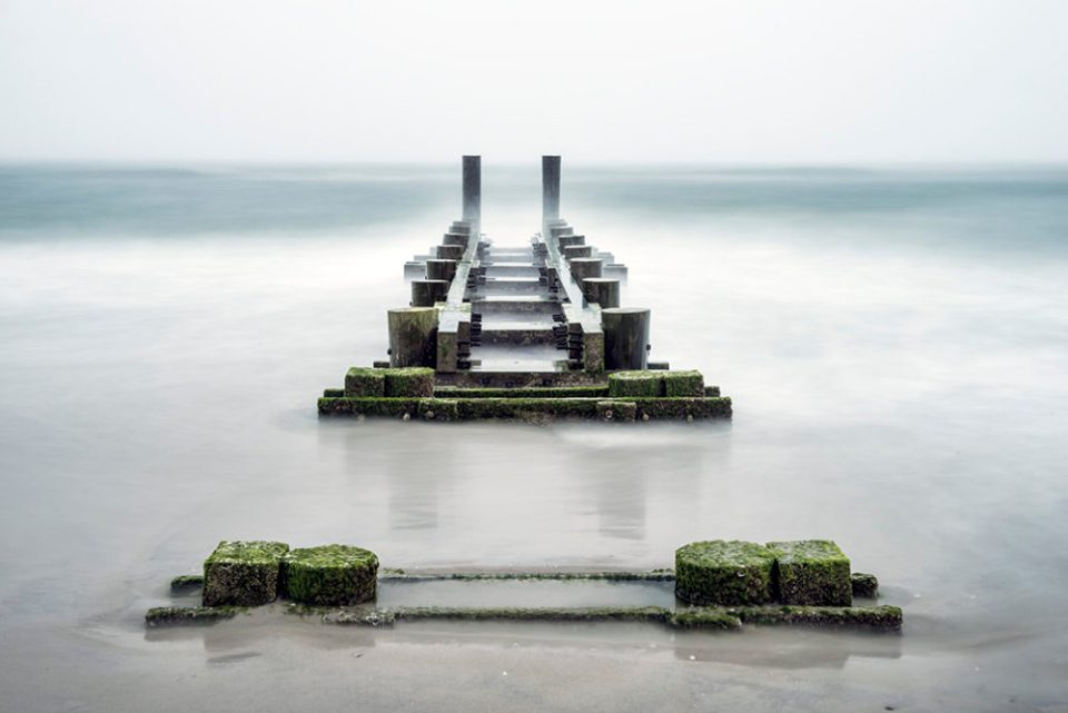 The pier isolated due to  negative space created by blurred waves and dense fog. © F.M. Kearney