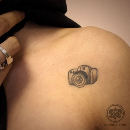 A black and grey tattoo of a small camera, in tribute of the woman's best friend. Designed and tattooed by Naomi Hoang at NAOHOA Luxury Bespoke Tattoos, Cardiff (Wales, UK).