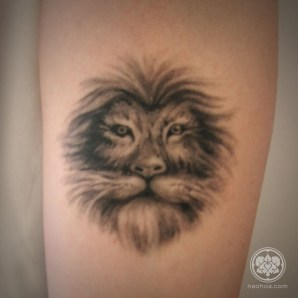Black and white lion tattoo on a woman's inner forearm.