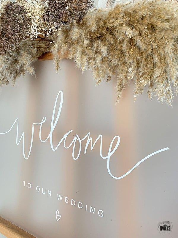 Gepersonaliseerd welkomstbord bruiloft frosted plexiglas handlettering closeup Studio Naokies