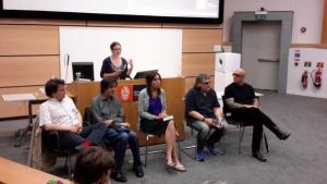 This image shows writers Frédéric Grellier, Romain Villet, Naomi Foyle, Rod Michalko and Ryan Knighton sitting on chairs arranged in a row in front of a long computer podium. Hannah Thompson is standing behind the podium, addressing the auditorium audience