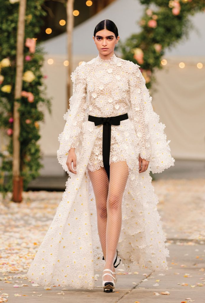 Haute couture short dress made of guipure lace with hand-embossed daisies, sewn-on cape and black grosgrain ribbon (price on request), Chanel