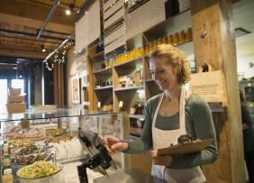 Woman at the register in a coffeeshop bakery