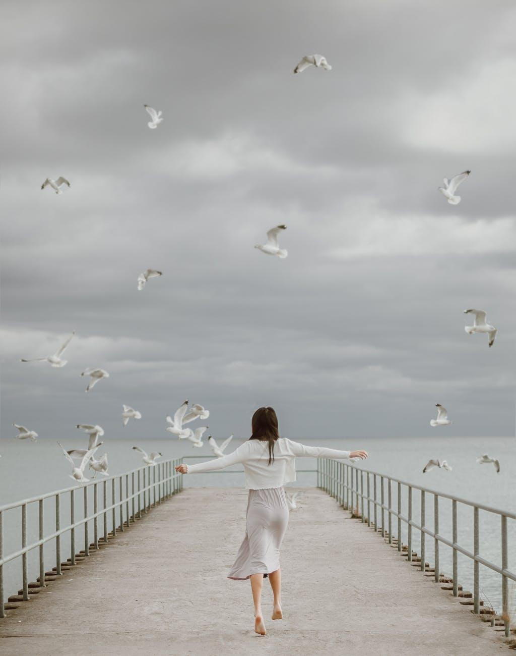faceless barefoot female traveler on embankment against sea