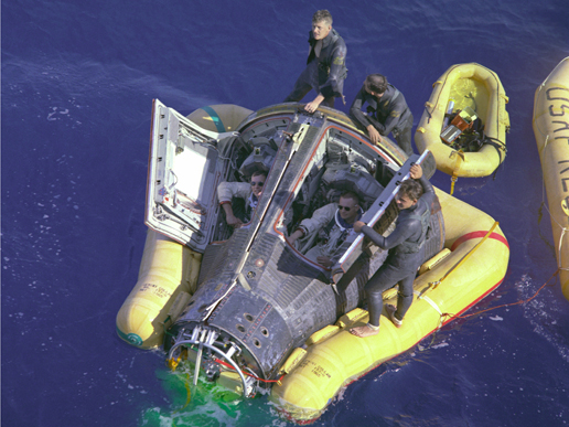 Astronauts Neil Armstrong and David R. Scott, assisted by U.S. Navy divers, await the arrival of the recovery ship after completion of their Gemini 8 mission.