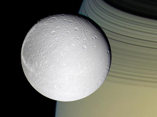 Saturn's moon Dione in the foreground is enriched by gold and blue hues of planet's rings in the background.