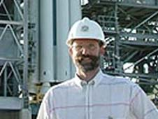 Phil Christensen stands in front of a rocket