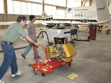 Gerry Heymsfield (pushing cart) and Lihua Li prepare to integrate the HIWRAP instrument on NASA's GlobalHawk this week in advance of the (GRIP) hurricane experiment.