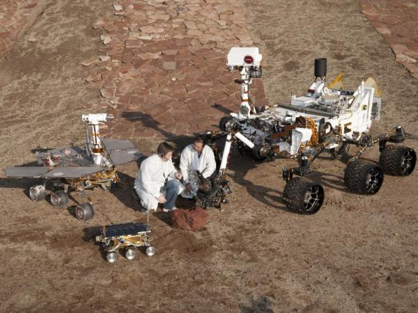 NASA Three Generations of Rovers with Crouching Engineers