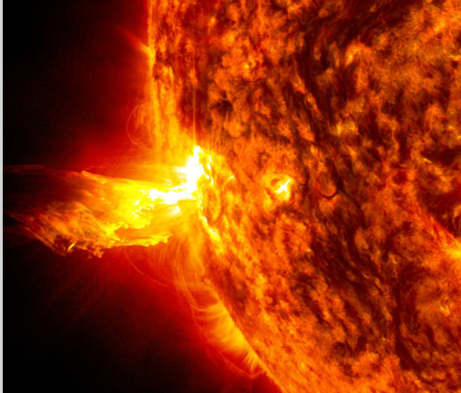 This image from June 20, 2013, at 11:15 p.m. EDT shows the bright light of a solar flare on the left side of the sun and an eruption of solar material shooting through the sun's atmosphere, called a prominence eruption.