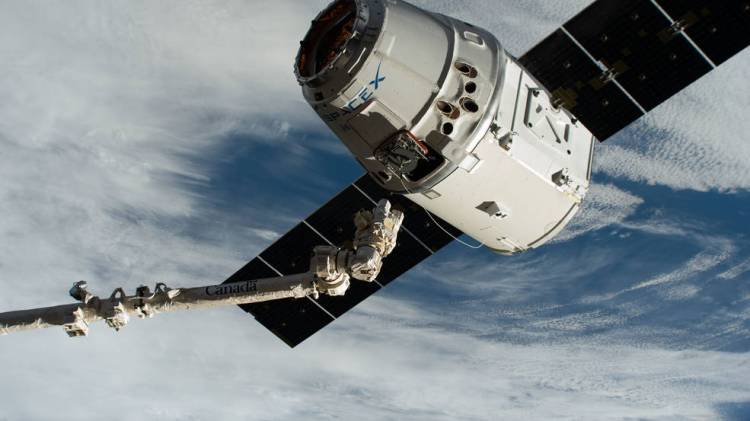 The Canadarm2 robotic arm, commanded by astronaut David Saint-Jacques, reaches out to grapple the SpaceX Dragon cargo craft