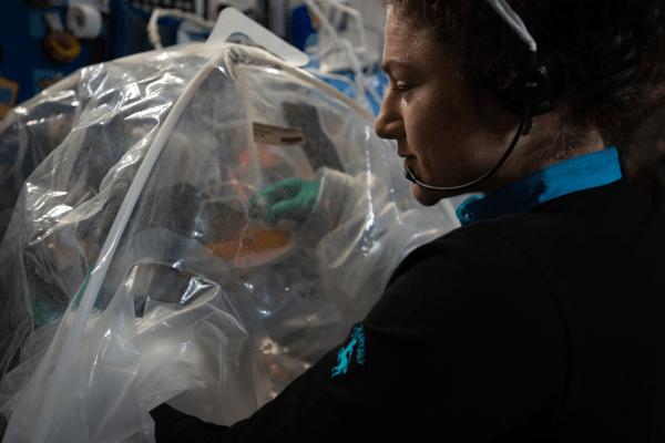 astronaut jessica meir working inside a glove bag