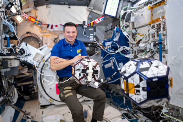 astronaut andrew morgan with the SPHERES satellites inside the space station