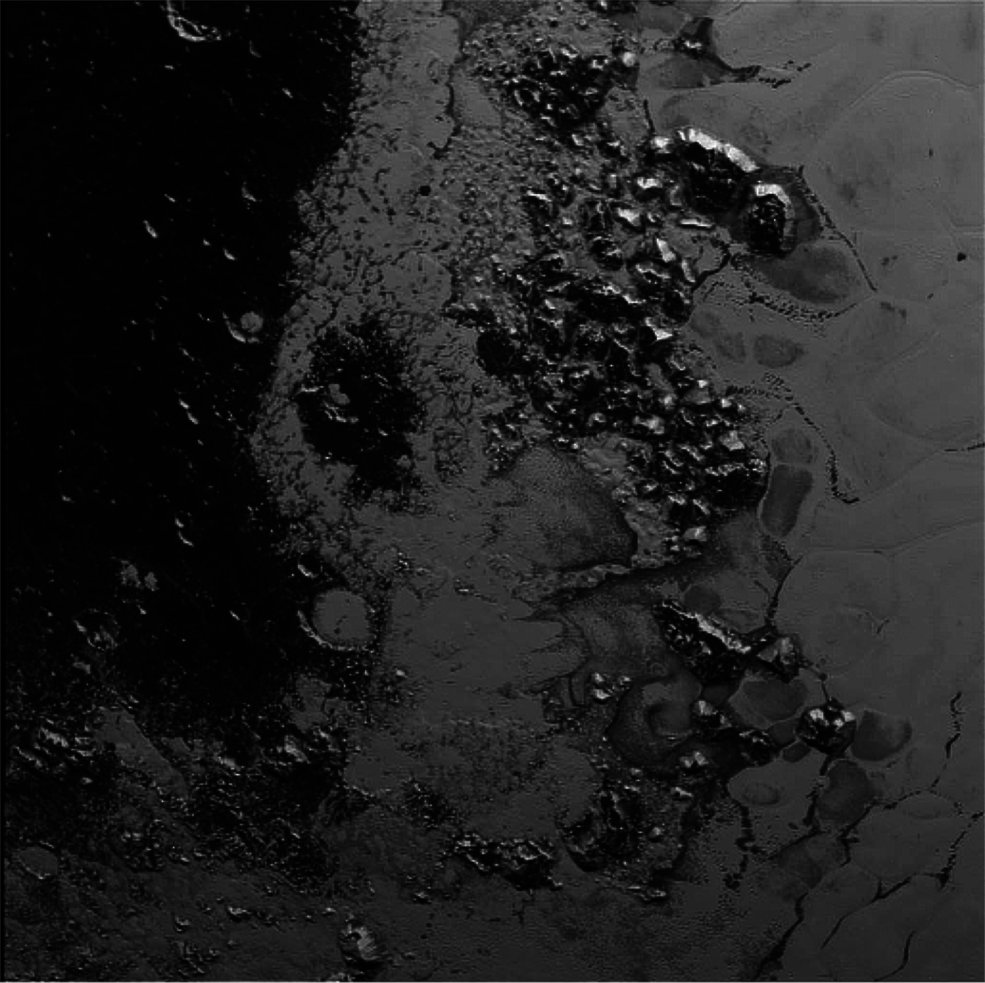 A newly discovered mountain range lies near the southwestern margin of Pluto's Tombaugh Regio (Tombaugh Region), situated between bright, icy plains and dark, heavily-cratered terrain. This image was acquired by New Horizons' Long Range Reconnaissance Imager (LORRI) on July 14, 2015 from a distance of 48,000 miles (77,000 kilometers) and received on Earth on July 20. Features as small as a half-mile (1 kilometer) across are visible. Credits: NASA/JHUAPL/SWRI