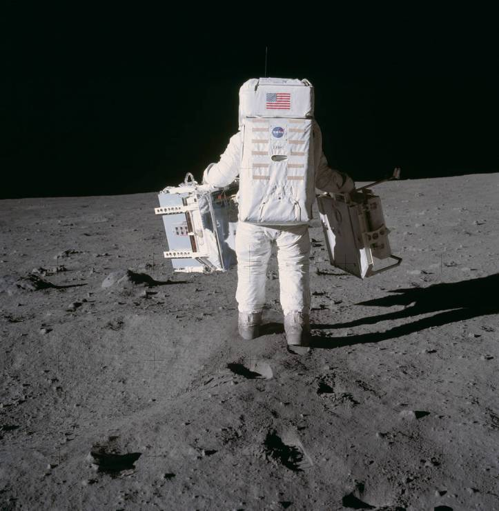 Buzz Aldrin in spacesuit holding experiment packs walking on lunar surface