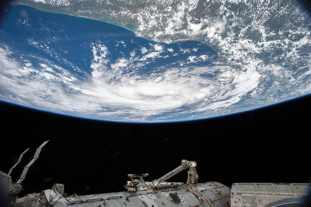 Earth from space with tropical storm visible above and space station's robotic arm below