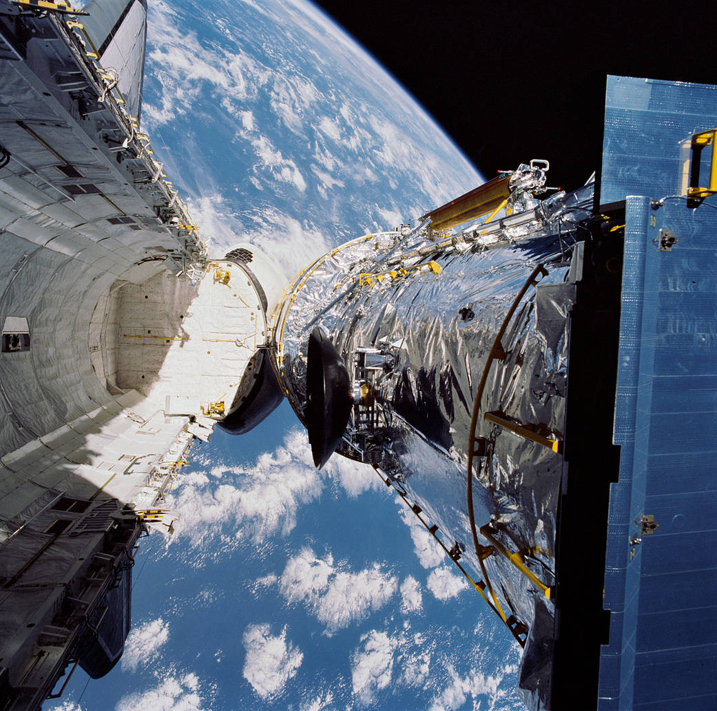 Space shuttle cargo bay open and space telescope being released, with Earth visible below