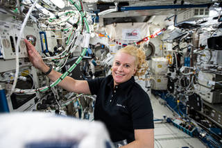 astronaut Kate Rubins working on research hardware inside the space station