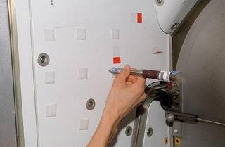 Astronaut Sunita Williams uses the swabbing unit to collect samples that will be placed into the cartridges