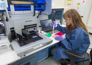 Scientist, to the right, sitting at a lab desk pipetting into a set of samples. There's a large machine to the left.