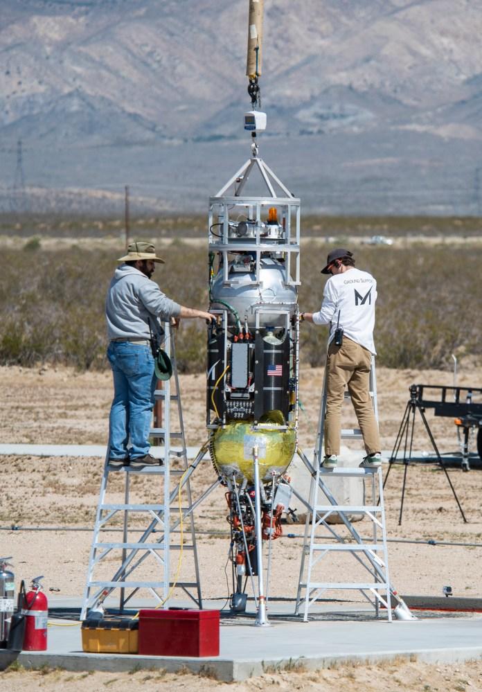 Masten Space Systems' technicians prepare their Xodiac rocket to flight test Honeybee Robotics pneumatic sampler collection system, PlanetVac, in Mojave Desert. Credits: NASA Photo / Lauren Hughes