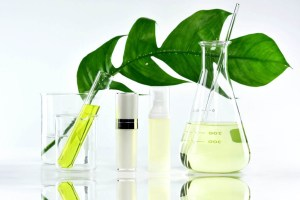 Different sized beakers holding light green clear liquid with a green leaf in the background