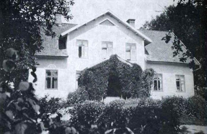 Näshults prästgård på 1920-talet. Rundeln på gårdsplanen är full med blommor och verandan är inklädd i grönt. Stora träd skuggar infarten till prästgårdsbyggnaden.