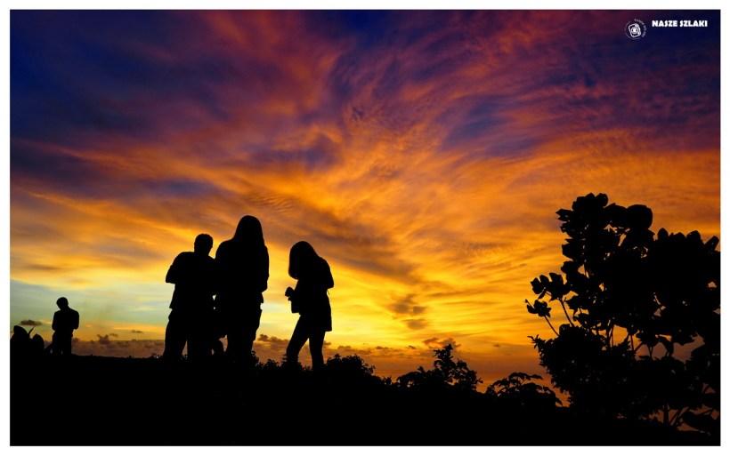 Zachód słońca, kolorowe niebo, ludzie na plaży, roślinność na tle kolorowych chmur,