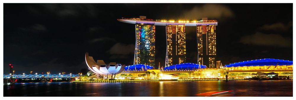 Hotel Marina Bay Sands od strony Clifford Square, pokaz laserów, światła i muzyki. Po zatoce pływają łodzie a brzeg jest kolorowo oświetlony, ArtScience Museum