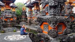 Ubud na Bali miasto artystów i rzemieślników. Przydomowa świątynia lub kaplica. Balijczyk podczas modłów.